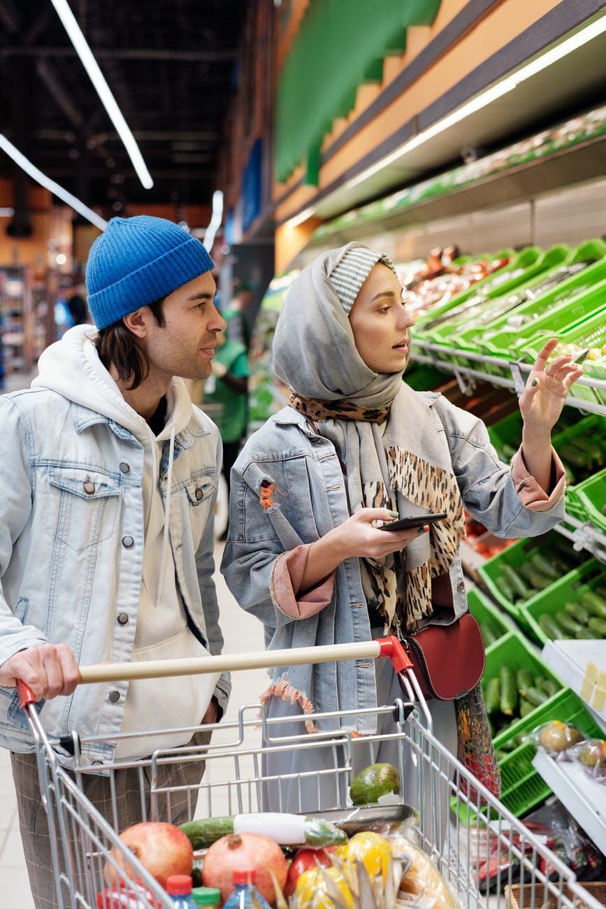 Wanita berhijab belanja buah-buahan di supermarket ditemani suami. Stroke pada Wanita