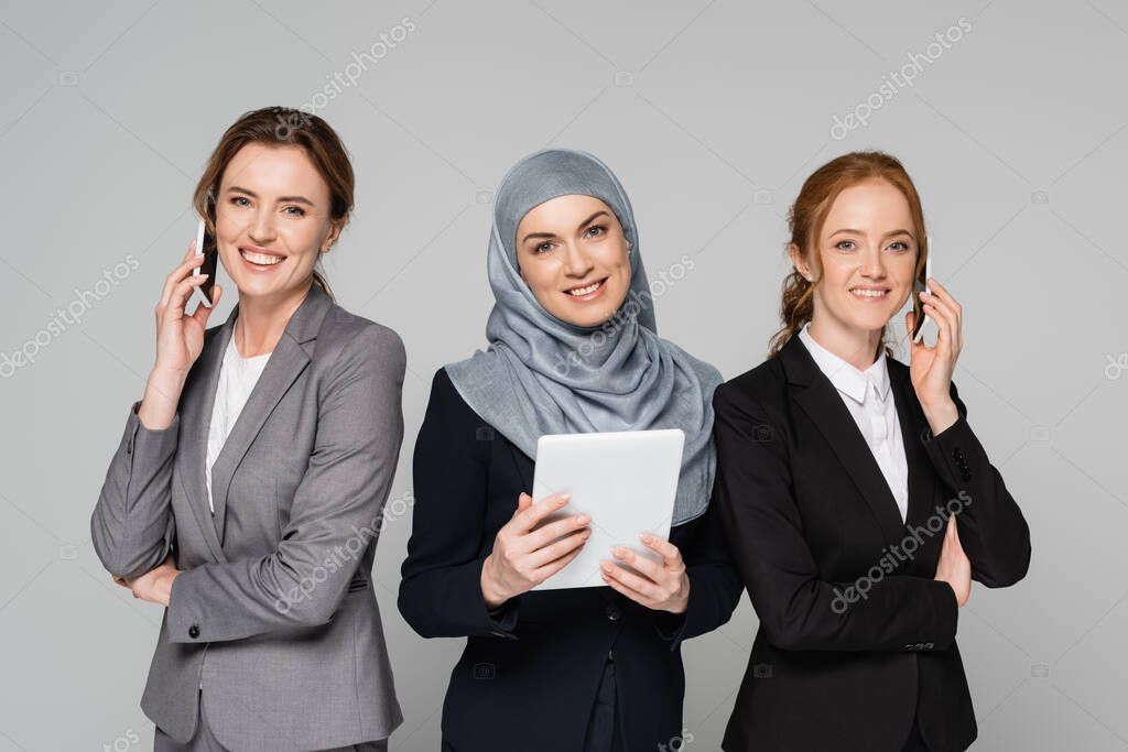 Arabian businesswoman holding digital tablet near colleagues talking on smartphones isolated on grey