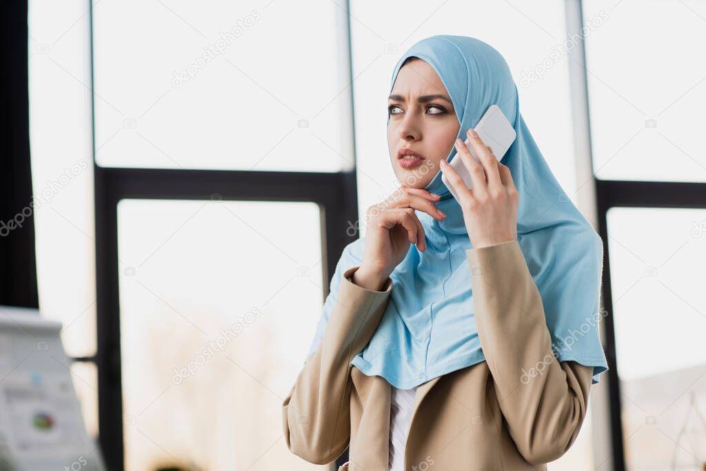 thoughtful arabian businesswoman in hijab talking on cellphone in office